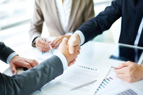Image-of-business-partners-handshaking-over-business-objects-on-workplace Эквайринг - прием платежей и быстрая техподдержка